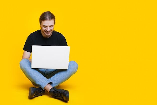 L'uomo barbuto caucasico con i capelli lunghi è seduto su un muro giallo con spazio libero e lavora al pc
