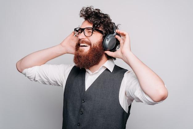 Il giovane allegro barbuto sta ascoltando la musica con le cuffie