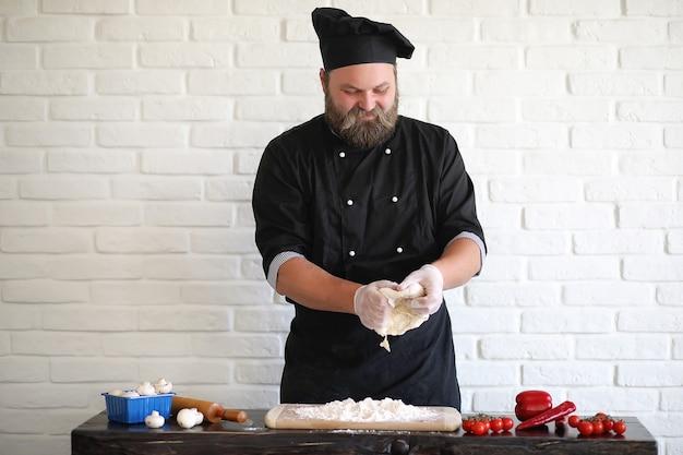 Lo chef chef barbuto prepara i pasti al tavolo in cucina