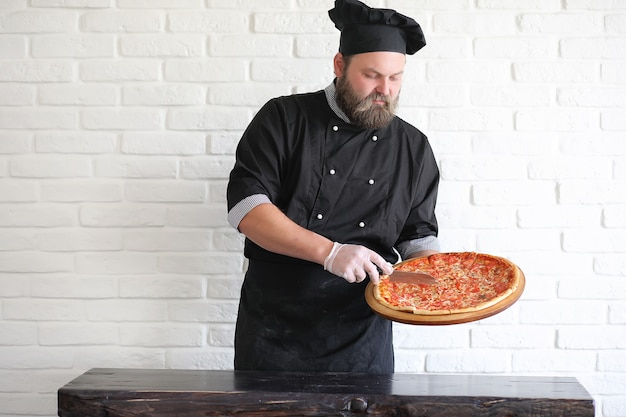 Lo chef barbuto prepara i pasti al tavolo in cucina