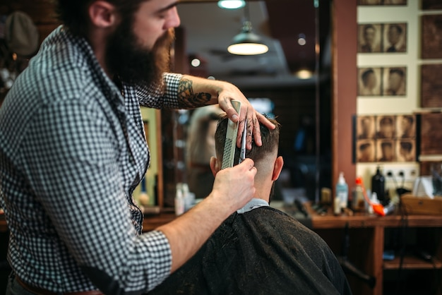 Acconciatura di taglio coiffeur barbuto con le forbici. uomo cliente in capo salone nero seduto contro uno specchio dal barbiere
