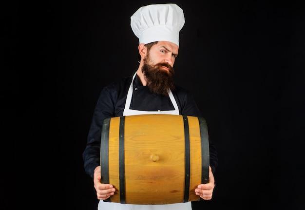 Cuoco barbuto con botte di legno. attrezzatura per la preparazione della birra. celebrazione del festival dell'oktoberfest.
