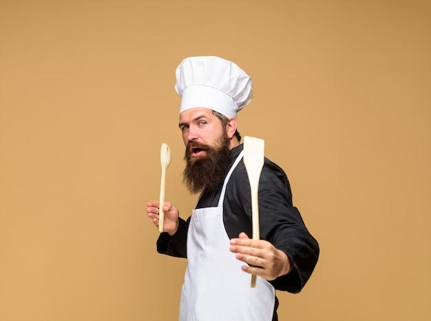 Cuoco barbuto con cucchiaio di legno e spatola in mano capo uomo in uniforme da cuoco tiene cucina in legno