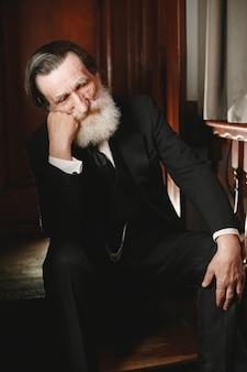 Barbuto anziano uomo d'affari. uomo in un ristorante. senior in abito nero.