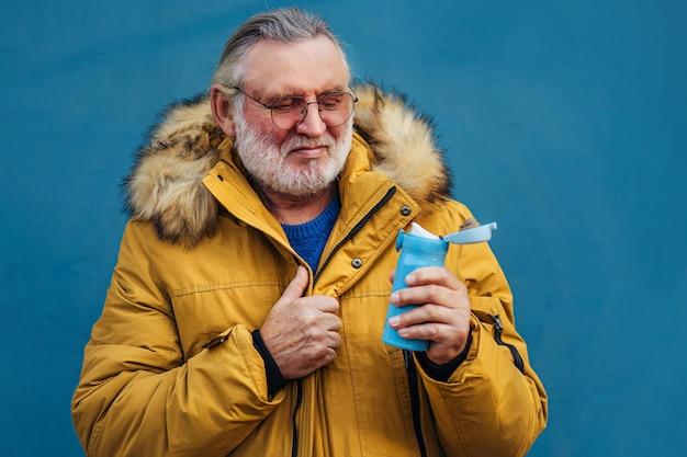 Maschio anziano barbuto che afferra un cappotto elegante mentre trasporta una bottiglia riutilizzabile
