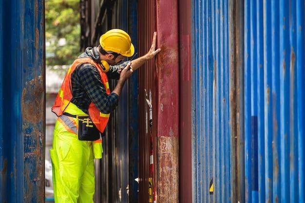 Ingegnere barbuto in piedi con il casco giallo per controllare il carico e controllare la qualità dei contenitori