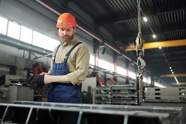 Barbuto ingegnere in abbigliamento da lavoro e elmetto protettivo in piedi da un enorme dettaglio di ferro mentre controlla il processo di lavoro in fabbrica