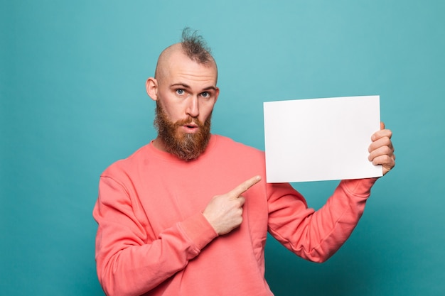 Barbuto uomo europeo in casual pesca isolato, che tiene il dito indice del punto del bordo di carta vuoto bianco