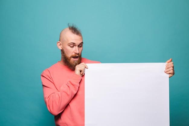 Barbuto uomo europeo in casual pesca isolato, che tiene il bordo di carta vuoto bianco con emozioni positive faccia stupita