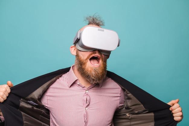 Barbuto uomo europeo in abito scuro isolato, indossando occhiali vr sulla testa con la bocca aperta del viso scioccato stupito eccitato