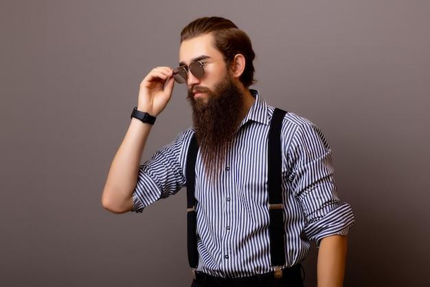 Ragazzo barbuto in camicia blu con acconciatura alla moda e barba lunga.