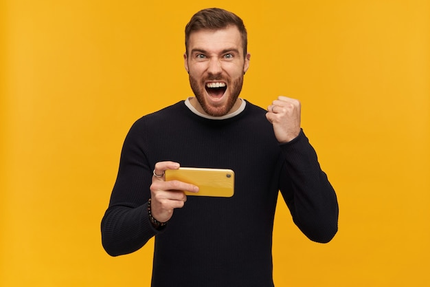 Ragazzo barbuto, uomo eccitato con capelli castani. ha il piercing. indossare un maglione nero. tenendo lo smartphone. pugno chiuso per celebrare la vittoria. isolato su muro giallo