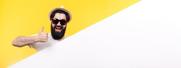 Ragazzo barbuto in occhiali da sole e cappello, un uomo tiene una bandiera bianca e mostra il pollice in su