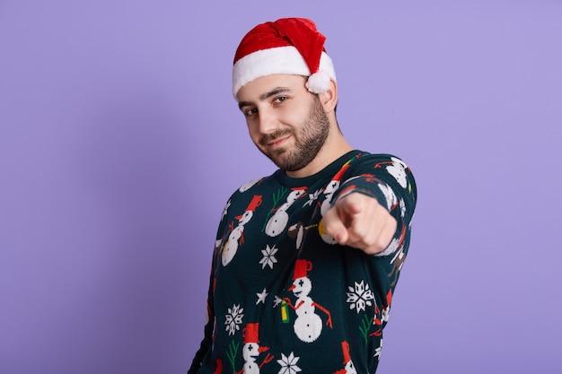 Ragazzo barbuto che indossa un maglione caldo che punta alla telecamera con il dito indice sulla viola
