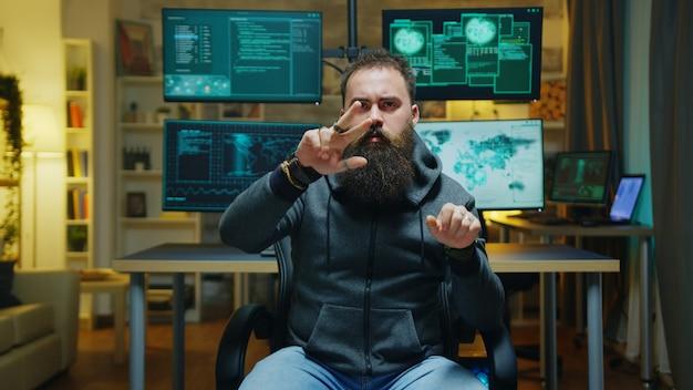 Hacker barbuto che fa gesti con le mani usando la realtà aumentata mentre rompe un firewall.