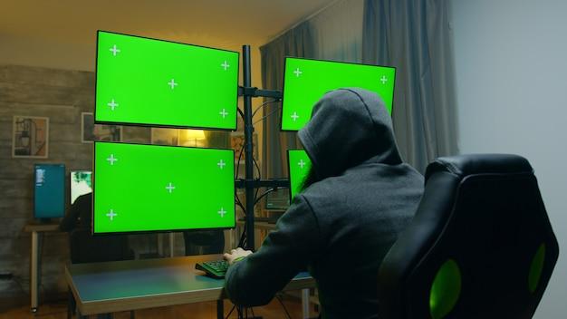 Hacker barbuto che nasconde la sua faccia indossando una felpa con cappuccio utilizzando un computer con schermi verdi.