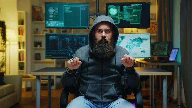 Hacker barbuto che indossa una felpa con cappuccio che utilizza la tecnologia aumentata per violare il firewall del governo.
