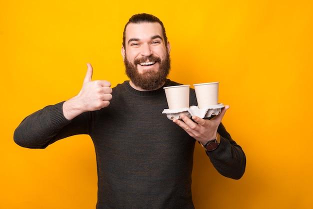 Uomo barbuto bello che mostra il pollice in su e che tiene il caffè da asporto su giallo