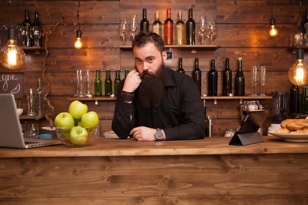 Barbuto bel giovane barista dietro il bancone del bar. orologio da polso fresco.