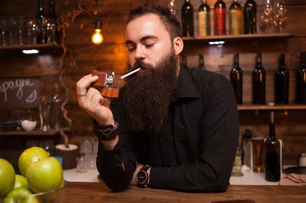 Barbuto bel giovane barista che accende la sua sigaretta in un pub o ristorante vintage