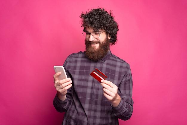 Uomo barbuto felice con il telefono e una carta di credito