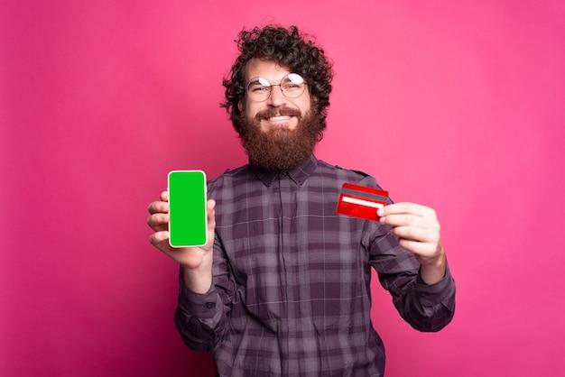 Barbuto uomo felice con tablet e una carta di credito