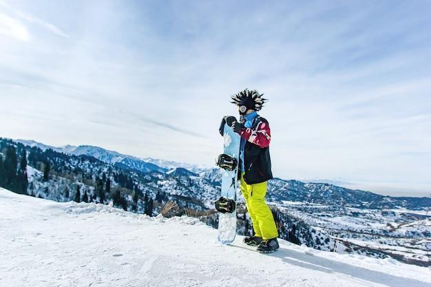 Snowboarder barbuto felice in una maschera da sci con occhiali e un grande cappello di pelliccia mohawk su uno sfondo di cielo