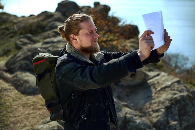 Un escursionista barbuto che tiene la mappa del percorso e lo guarda. un bellissimo paesaggio autunnale e lago. concetto di persone che viaggiano nella natura.