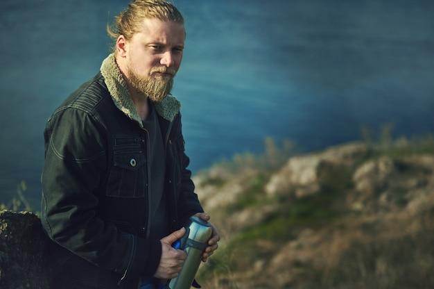 Viandante barbuto che riposa su una pietra e che tiene il thermos che esamina la distanza al lago
