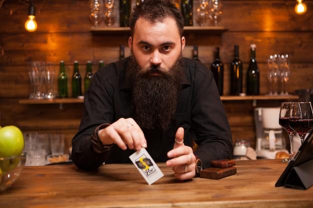 Barista hipster barbuto che gioca con le sue carte truccate. divertirsi.