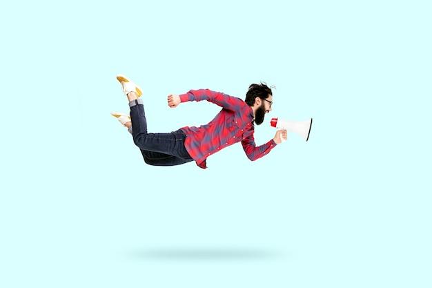 Uomo barbuto hipster in bicchieri, saltando e gridando nel megafono