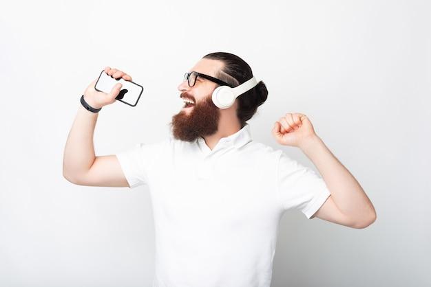 L'uomo barbuto hipster si sta divertendo mentre ascolta la musica.