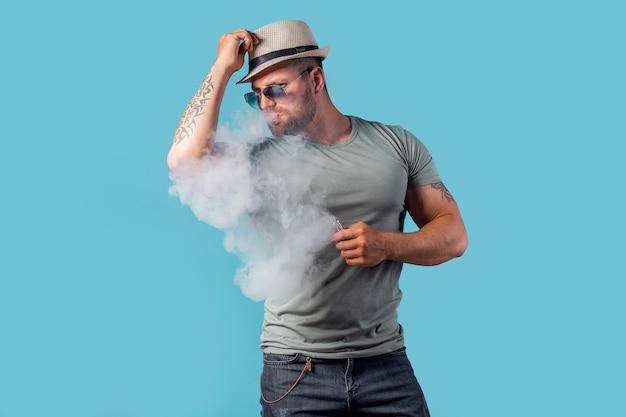 Maschio barbuto con cappello e occhiali da sole che fuma una sigaretta a vapore come alternativa al tabacco sul blu