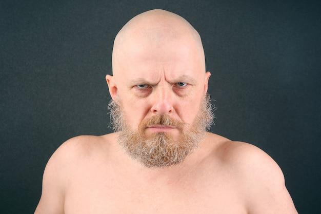 L'uomo barbuto dall'aspetto aggressivo guarda negativamente avanti