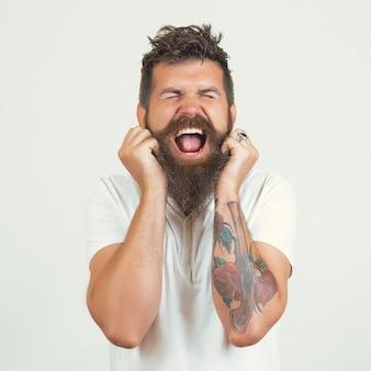 L'uomo barbuto urla con rabbia in uno sfondo bianco con spazio di copia. ritratto emotivo dell'uomo come barbaro. uomo barbuto hipster arrabbiato depresso che urla e grida bocca aperta, tenere la mano di testa