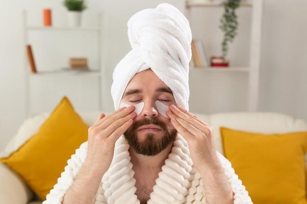 Uomo barbuto che applica bende sull'occhio sul suo viso. rughe e cura domiciliare del viso per gli uomini.
