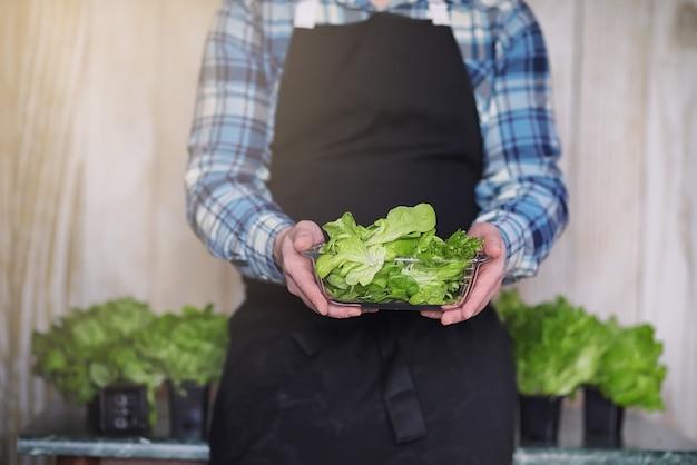 L'uomo barbuto in grembiule e guanti tiene una ciotola di insalata verde fresca