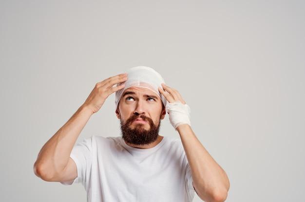 Uomo barbuto fasciato la testa e il trattamento del sangue della mano. foto di alta qualità