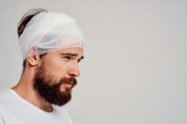 Uomo barbuto fasciato la testa e il trattamento del sangue delle mani