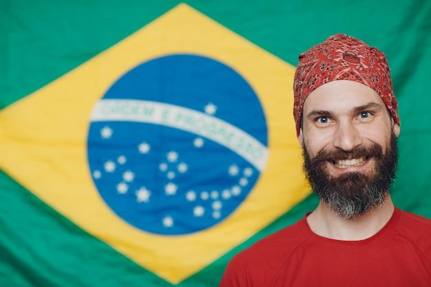 Uomo barbuto in bandana contro la bandiera brasiliana