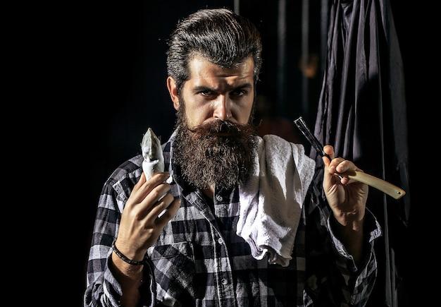 Uomo barbuto in negozio di barbiere forbici da barbiere e rasoio barbiere negozio di barbiere vintage negozio di barbiere rasatura ritratto uomo barbuto baffi uomini brutale ragazzo forbici rasoio