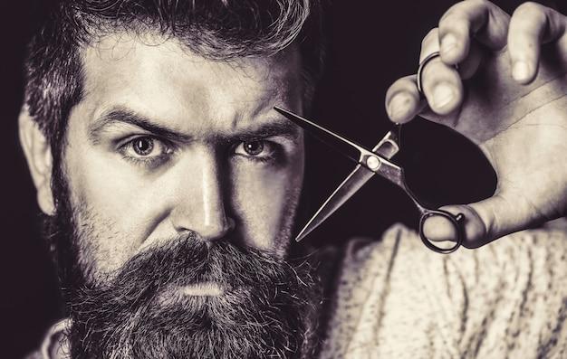Uomo barbuto, maschio barbuto. ritratto di barba uomo alla moda. forbici da barbiere e rasoio, negozio di barbiere. barbiere vintage, rasatura. bianco e nero.