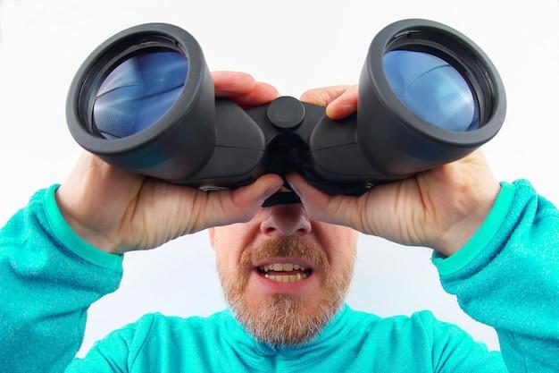 Uomo barbuto con una giacca blu che guarda attraverso il binocolo su uno sfondo chiaro. cerca il tuo obiettivo