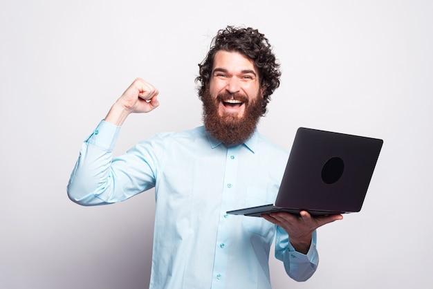 Uomo barbuto camicia blu che tiene laptop e celebra la vittoria sul muro bianco