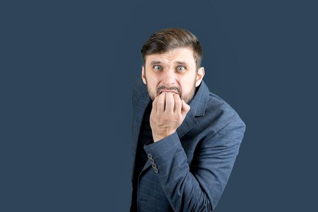 Un uomo con la barba in abito blu si morde le unghie per la paura