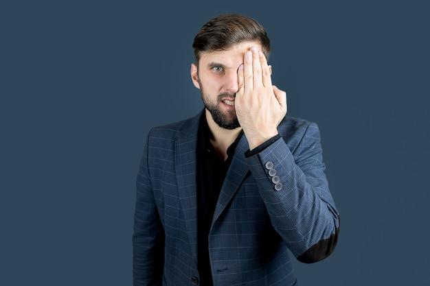 Un uomo barbuto con un vestito blu si coprì gli occhi con h