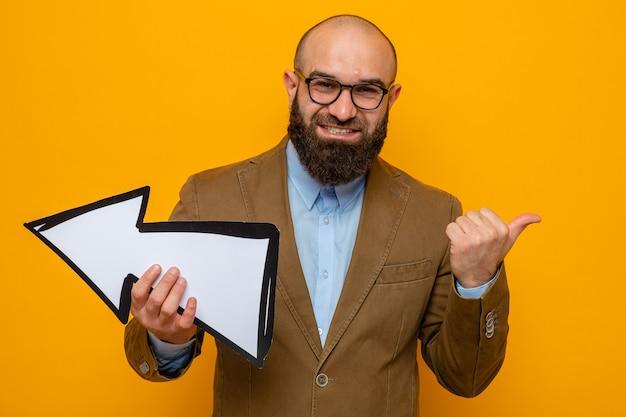 Uomo barbuto in abito marrone con gli occhiali tenendo la freccia guardando la telecamera sorridendo allegramente puntando con il dito indice sul lato in piedi su sfondo arancione