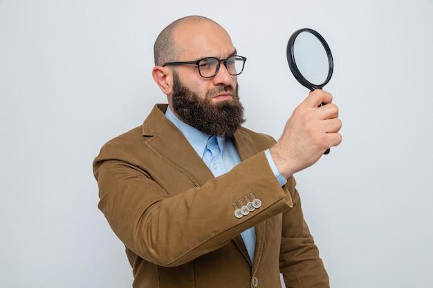 Uomo barbuto in abito marrone con gli occhiali che tiene la lente d'ingrandimento guardando attraverso di essa con una faccia seria in piedi su sfondo bianco