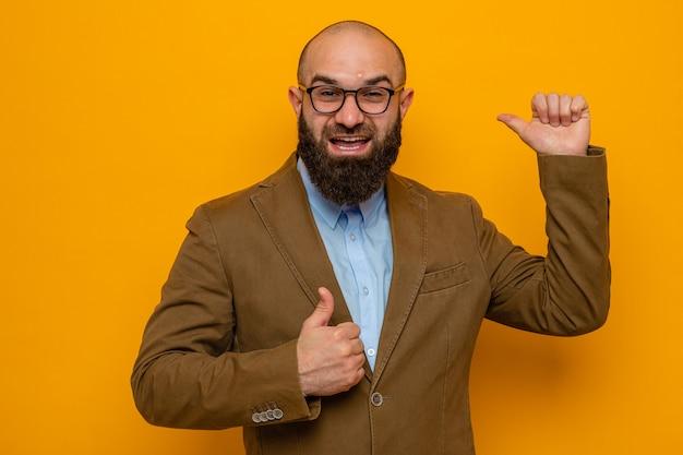Uomo barbuto in abito marrone con gli occhiali che guarda la telecamera felice e positivo che mostra i pollici in su che puntano indietro con il pollice in piedi su sfondo arancione orange