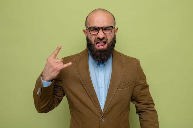 Uomo barbuto in abito marrone con gli occhiali che sembra felice ed eccitato che tira fuori la lingua che mostra il simbolo del rock